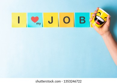 """Concept of """"I love my job"""" with multicolored sticky notes and hand holding a paper cup with happy smile cartoon on blue background and blank space for text"""