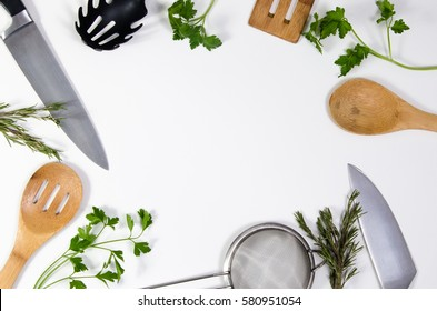 Concept idea for advertising or presentation in food industry, menus, brochures for restaurants. Copy space or room for text on white background, with kitchen utensils and parsley leaves scattered.