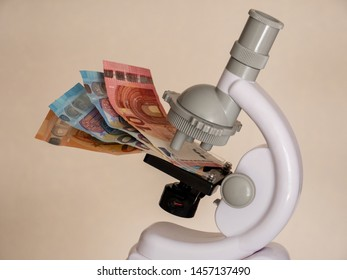 Concept Idea: Microscope as a symbol of science and banknote as a symbol for project financing
