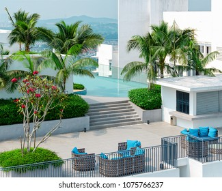 Concept of ideal exotic vacation - top view of beautiful roof top with swimming pool, lounge zone, green trees, palm, mountains on horizon. Fantastic terrific romantic landscape. Malaysia, Cyberjaya.