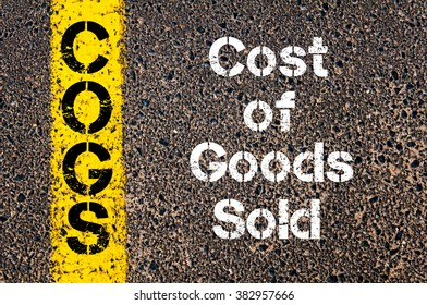 Concept image of Business Acronym COGS Cost Of Goods Sold written over road marking yellow paint line