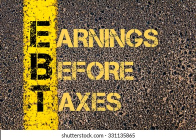 Concept image of Business Acronym  EBT as EARNINGS BEFORE TAXES written over road marking yellow paint line.