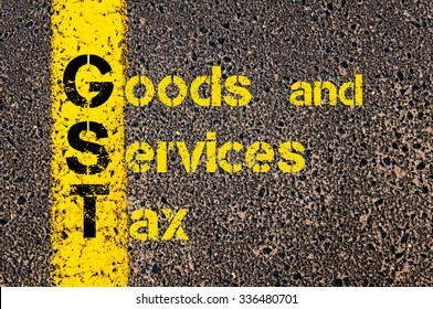 Concept image of Business Acronym GST as Goods and Services Tax written over road marking yellow paint line.