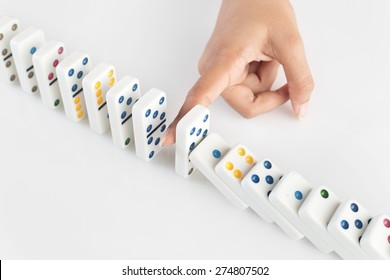 Concept image for business strategy and solution to crisis. Concept for  solution for  crisis situation, stopping a chain reaction of failures. Human finger stopping the domino effect. S