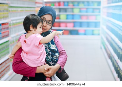 Concept image of buying in Malaysia. Mother and her daughter shopping in a Tesco Hypermarket with blurry background of groceries on the rack with copy space.