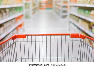 Concept image of buying. Shopping trolley in a Tesco Hypermarket with blurry background of groceries on the rack. Focused only at the trolley.