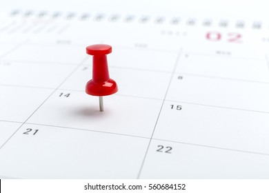 Concept image of a Calendar with a red push pin. Closeup shot of a thumbtack attached. The words heart shape written on a white notebook to remind you an important appointment.
