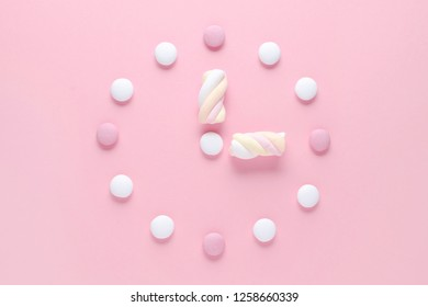 concept image, a clock with candy and marshmallow, pastel colors on pink