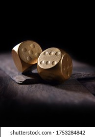 Concept image for financial gamble or casino gambling. Two gold dice against a black background with generous accommodation for copy space.