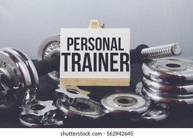 A Concept image of Fitness or bodybuilding background with a dumbbell and extra plates. Vintage tone and a wooden stand with a white frame and a word Personal Trainer
