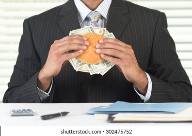 Concept image for greedy corporate business people. CEO is eating a burger stuffed with currency. He is at his desk in his office, wearing a black suit and tie.