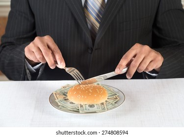 Concept image for greedy corporate executives and financial fraud. Executive is eating a burger on a plate stuffed with dollar bills. He is wearing a black suit and blue tie.