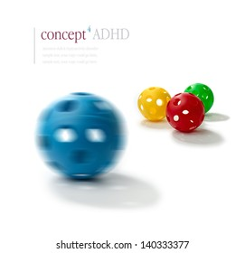 Concept image illustrating Attention Deficit Hyperactivity Disorder (ADHD). Spinning  plastic ball with illusion of two eyes and a mouth in foreground with normal balls in background. ADHD concept.