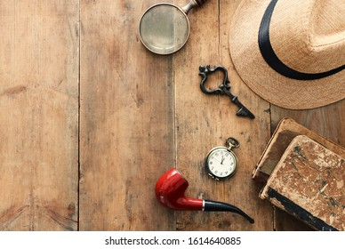 Concept image of investigation or private detective. Fedora hat, magnifying glass and vintage items over wooden table