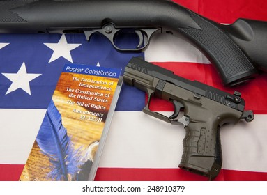 A concept image of liberty showing a pistol and rifle with the constitution booklet on the American flag,