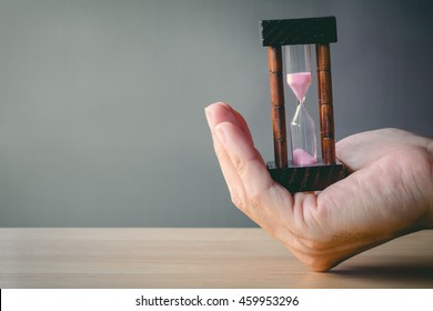 Concept image of management at the time of life. Abstract hourglass on man hand. passing time in a countdown sandglass with copy space for add text.