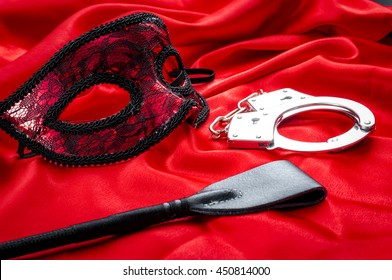 Concept image with a mask, hand cuffs and a flogger covered in rose petals on red silk. BDSM is a variety of erotic practices or role playing involving bondage, dominance and submission, sadomasochism