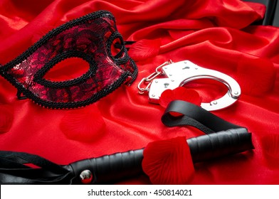 Concept image with a mask, hand cuffs and a flogger covered in rose petals on red silk. BDSM is a variety of erotic practices or role playing involving bondage, dominance and submission, masochism