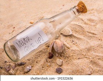 Concept image of NEVER GIVE UP message written on a piece of paper in a glass bottle on beach sand