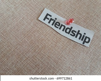 Concept image of newspaper cut word-Friendship pinned on the brown mat.Selective focus.