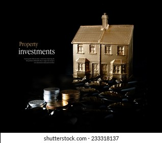 Concept image for property investment. Creatively lit gold house and stacked coins against a black background. Copy space.