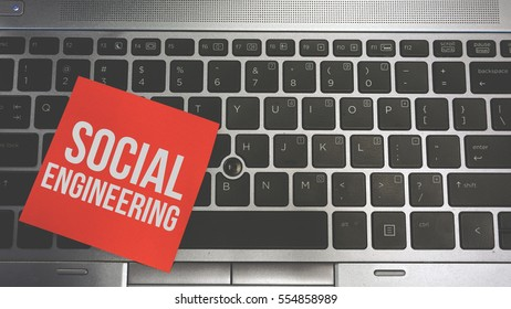 Concept Image of a red sticky note pasted on a keyboard with a message word white in color SOCIAL ENGINEERING
