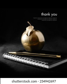 A concept image for rewards and success. A gold apple on a notebook with a gold pen against a black background. Copy space.