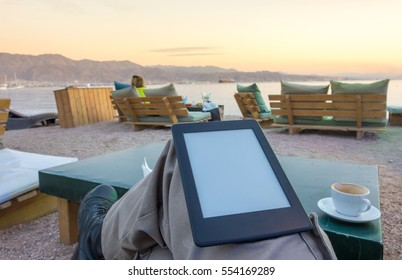 Concept image with room to paste text: enjoying an e-book / e-reader and a cup of afternoon cappuccino coffee on beach