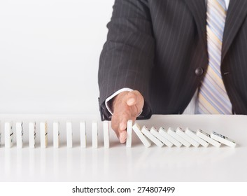 Concept image for solving problems. Image shows a business man wearing a black suit stopping falling dominoes. Image illustrates the concept of business strategy and solution to problems