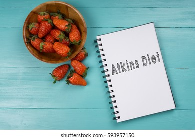 Concept image, strawberry with notebook on a blue wooden background with words Atkins Diet. Health concept.