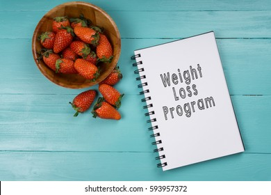 Concept image, strawberry with notebook on a blue wooden background with words Weight Loss Program. Health concept.