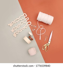 Concept image of tools for DIY projects including macrame threads, gold scissors, tapes and key chains, top view creative project concept on orange and green background