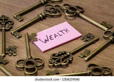 concept image using old keys and a tag with the word wealth handwritten on it over a wooden background