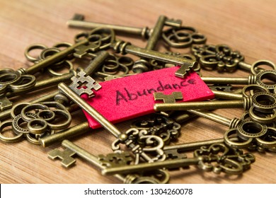 concept image using old keys and a tag with the word abundance handwritten on it over a wooden background