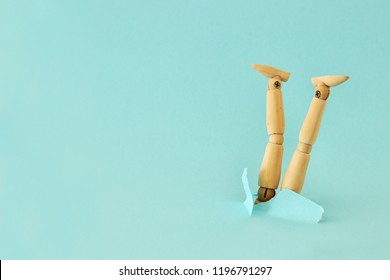 concept image of wooden dummy stuck upside down.  stress and danger concept.