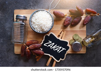 Concept image of Zakat in Ramadan. Image contain rice, dates and coins on a wood over nice dark hard textured background.  A chalkboard with 'ZAKAT' text inserted