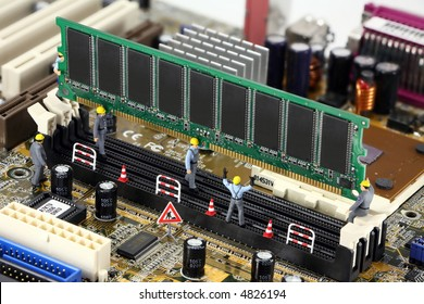 Concept images of miniature construction workers installing computer memory on a motherboard.