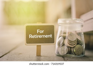 concept image,word RETIREMENT on wooden signage and coin in jar .fade color effect wooden background with light effect