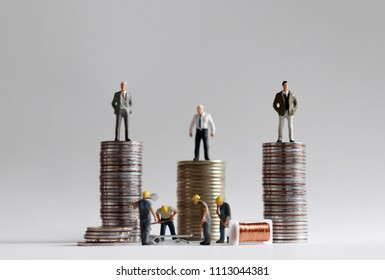 The concept of income gap. The stack of coins with miniature people.