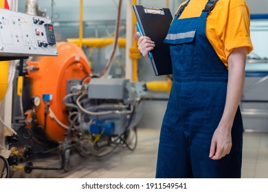 Concept of industrial production and factory. A female worker in uniform with a folder in her hand. In the background, boiler equipment.