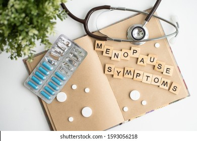 Concept. The inscription from the letters menopause. Symptoms of Menopause Harmonious changes in women older than 40 years.
