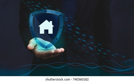 Concept For Insurance Company to Safe and Supporting Customer, House icon inside a Shield Guard to Protected them from Rain and Flood over a Businessman Hand