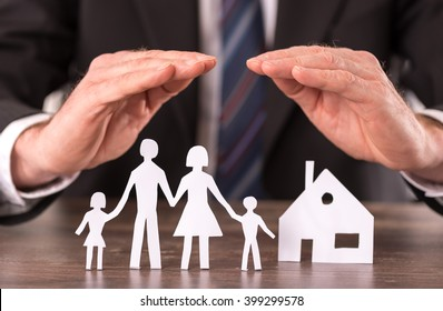 Concept of insurance with hands over a house and a family
