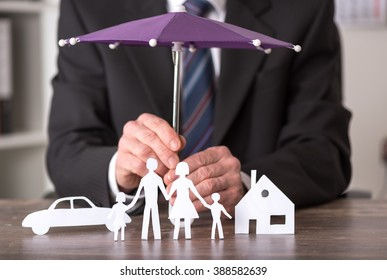 Concept of insurance with umbrella over a house, a car and a family