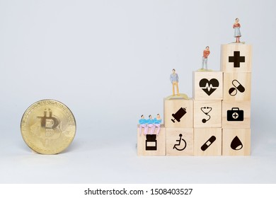 Concept of insurance for your health on wooden block with healthcare medical icon, miniature and Bitcoin. Bitcoin is a method for bill settlement in future.