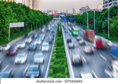 Concept of interaction between nature and technology - green trees and dividing green line along busy road, protect environment. Cars on highway in busy city, Air pollution. Photo with blur in motion.