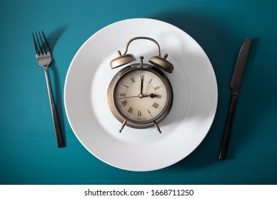 concept of intermittent fasting, ketogenic diet, weight loss. fork and knife on a plate and alarmclock