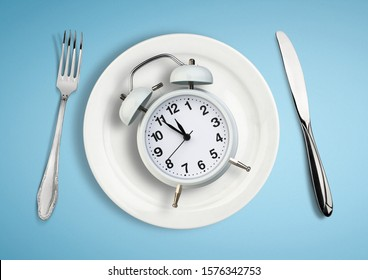 Concept of intermittent fasting, lunchtime, diet and weight loss. Clock on plate.