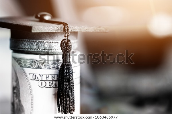 Concept of international graduate study, graduation black cap on pile of foreign money US dollars money on blur background. Education certificate of Abroad program to success. Vintage style