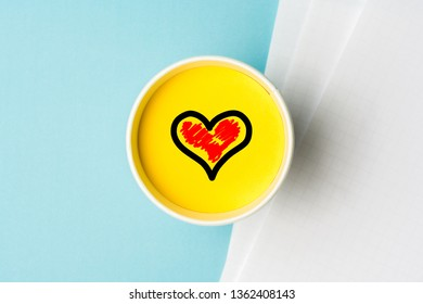 Concept for internet online dating or passion for job. Desk with paper sheets on blue background, and a paper cup with red heart symbol on yellow top.